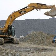 Excavator Moves Rocklift While Gripping Boulder